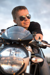 Romantic portrait handsome biker man sits on a bike