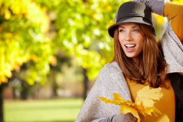 Young woman with autumn leaves in hand and fall yellow maple par