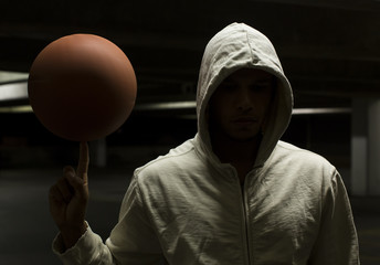 Anonymous street ball basketball player spinning a ball at night