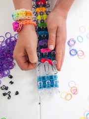 childs hands with loom and multicoloured elastic bands