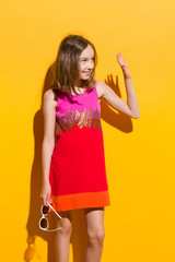 Girl in mini dress waving hand and looking away.