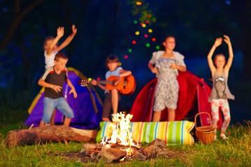 kids having fun around campfire. focus on fire