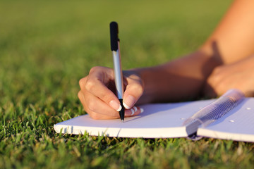 Close up of a woman hand writing on a notebook outdoor