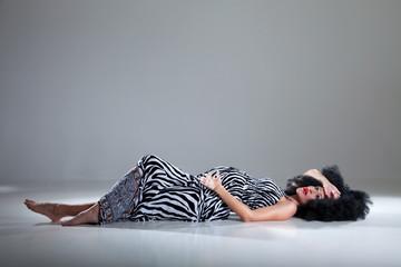 Schwangere hübsche Frau liegt am Boden im Zebra Kleid