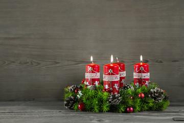 Dritter Advent: Adventskranz mit drei roten brennenden Kerzen