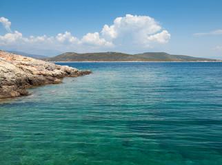 rocky coast with green sea and blue sky