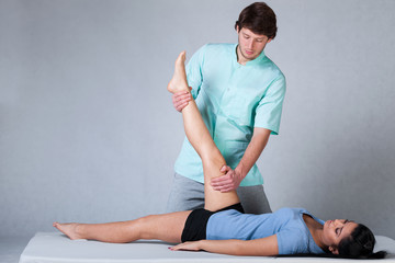 Physiotherapist stretching patient