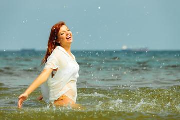 Vacation. Girl splashing water having fun on the sea.