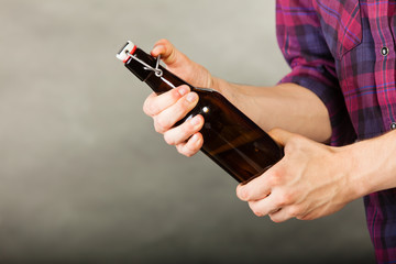 young man holding a beer bottle on grey