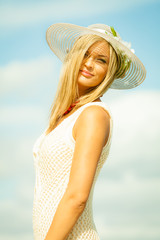 Beautiful blonde girl in hat on beach, summertime