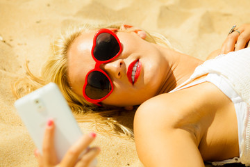Teen girl with mobile phone on beach