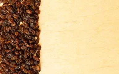 Border frame of raisin on wooden table background