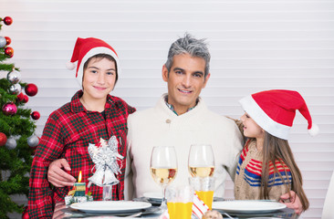 Happy father with son and daughter celebrating Christmas at home