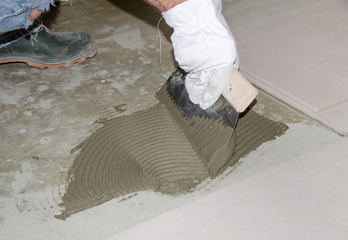 Tiler spreading tile adhesive on the floor