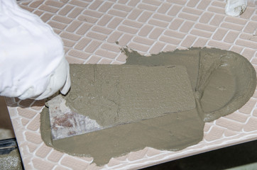 Tiler spreading tile adhesive on the back of a tile
