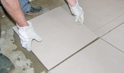 Tiler laying a new tile on the floor