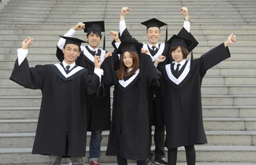 graduates posing holding their diploma  of the university