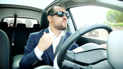 Business man with sun glasses driving car dancing