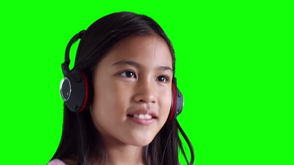 little girl listening to music on headphones, Green screen