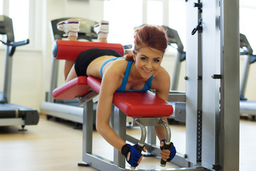 Cheerful girl posing exercising on bench in gym