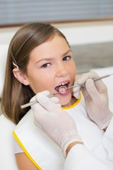 Pediatric dentist examining a little girls teeth