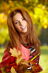 Beautiful elegant woman  in a park in autumn
