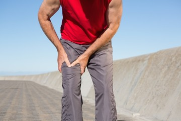 Active senior man touching his injured thigh