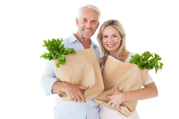 Happy couple carrying paper grocery bags