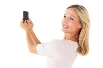 Happy blonde sending a text message