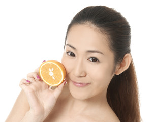 Portrait of an attractive young girl holding a slice of orange