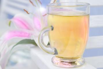 filiżanka z herbatą na tle różowy kwiat