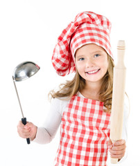 Smiling cute little girl in chef hat with ladle and  rolling pin