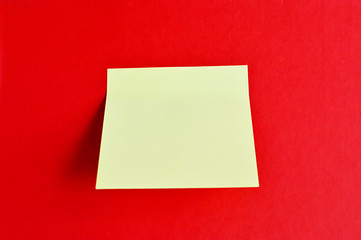 Yellow paper note isolated on a red background