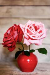 Zwei Rosen in roter Vase vor rustikalem Hintergrund