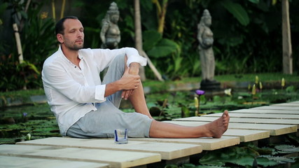 Young man looking around, relaxing in exotic garden