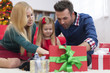 Impatient little girl opening christmas presents with parents