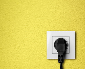 black cable plugged in a white electric outlet