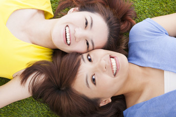 two  pleasure young woman lying on grassland