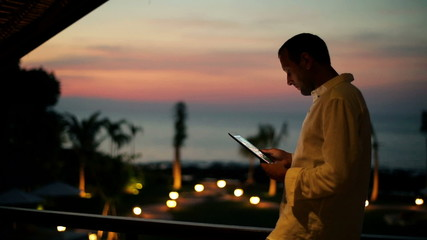 Young man with tablet standing on terrace at night