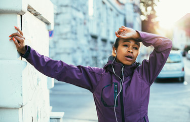 Tired young woman catching breath after training in city