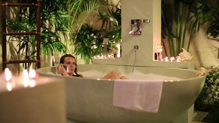 Woman talking on cellphone while lying in bathtub at night