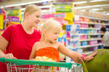 Young mother and adorable girl in shopping cart looks at giant j