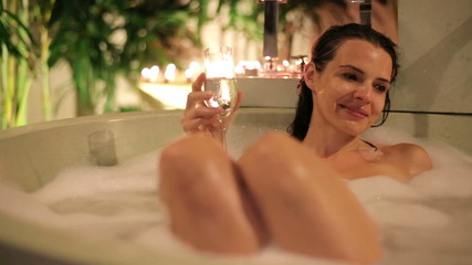 Woman drinking champagne, relaxing in bathtub at night