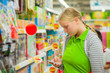 Young mother look at shopping list in phone in supermarket