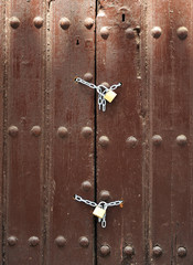 Puerta de madera cerrada con cadenas y candados