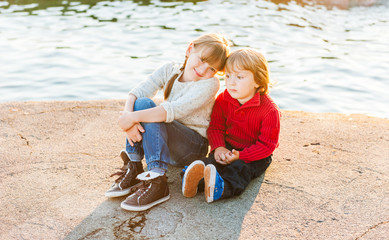 Sunset portrait of adorable children resting next to lake