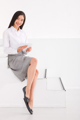 Businesswoman sitting stairs holding digital tablet