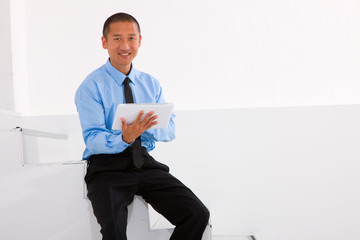 Businessman sitting stairs holding digital tablet