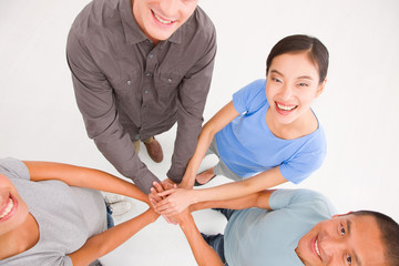 Businesspeople standing in a circle placing their hands top of e