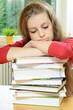 Schülerin erschöpft auf Buch-Stapel